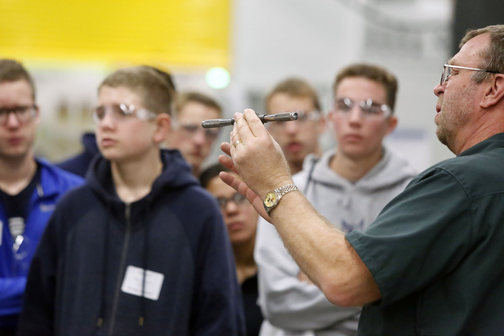 man demonstrates use of manufacturing tool to high school students on a tour of factory floor