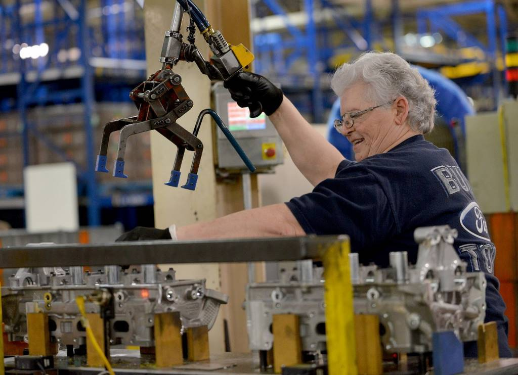 Elderly white haired woman works on auto assembly line