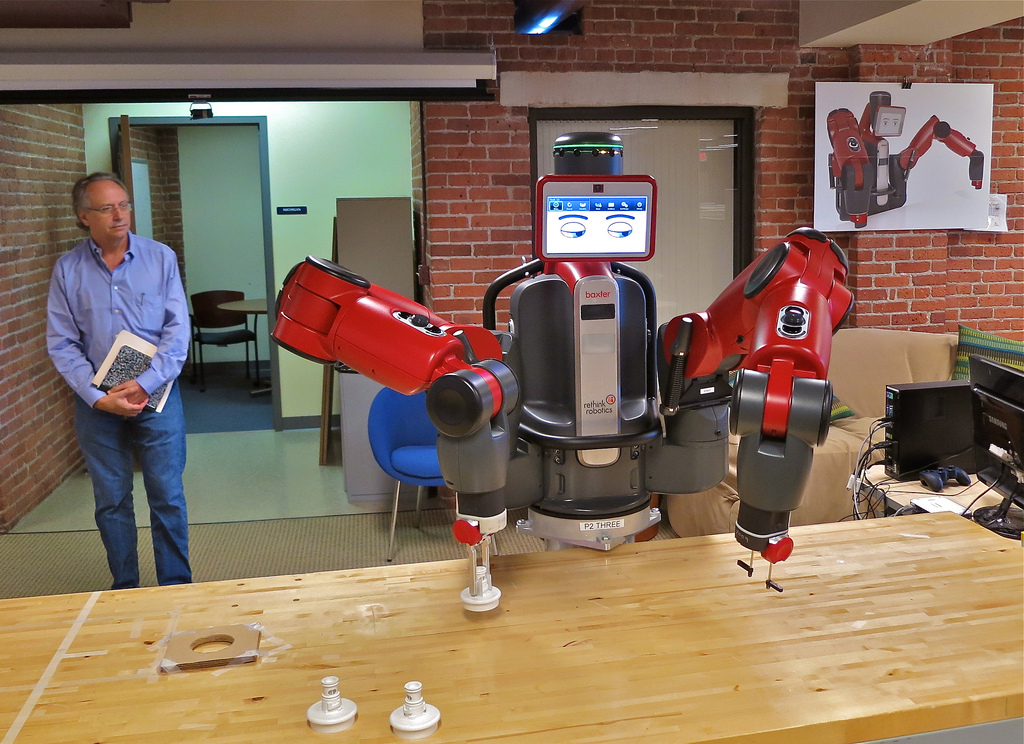 Red Baxter robot performs manufacturing task as man watches in the distance